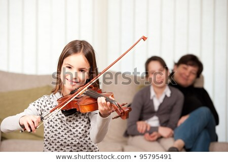 Girl playing violin to family Stock photo © IS2