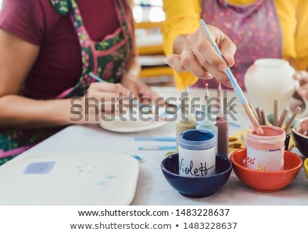 Woman coloring handmade dishes using brush and color Stok fotoğraf © Kzenon