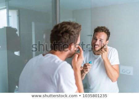 Happy young man taking care of his undereye wrinkles putting anti-aging eye cream Stock photo © Maridav