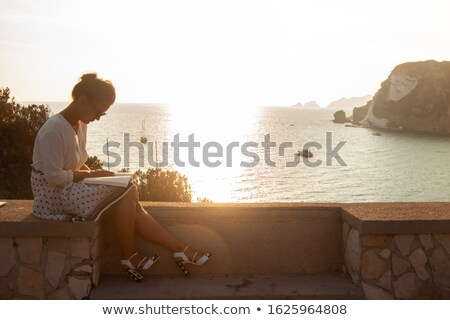 Stock photo: Silhouette of the young woman sitting close to the sea