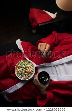 man in a santa suit smoking and eating popcorn Stock photo © nito