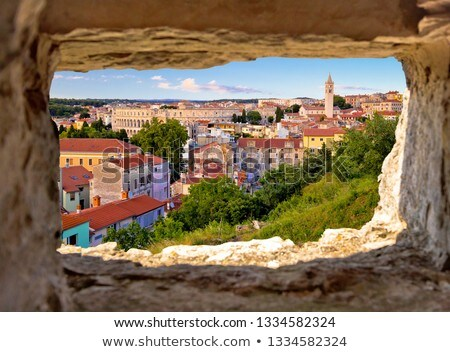 panoramic view of pula landmarks through stone window stock photo © xbrchx