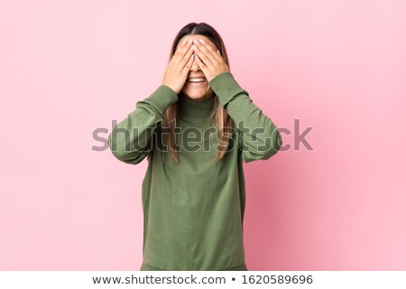 Portrait of caucasian joyful woman covering eyes to excited girl Stock photo © deandrobot