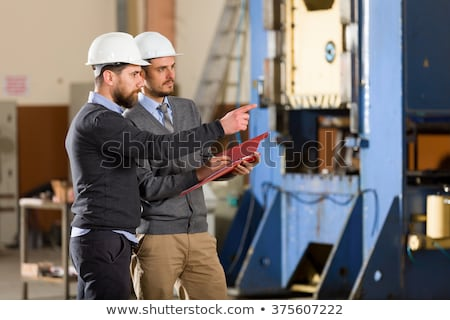 businessman in helmet with clipboard at warehouse Stock photo © dolgachov