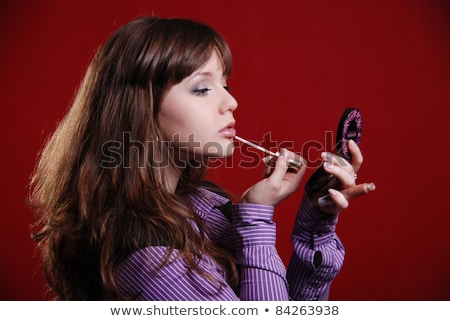 Cheerful pretty young woman holding mirror and applying lipstick Stock photo © deandrobot
