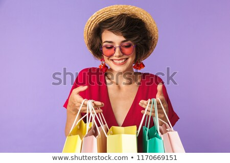 Photo of shopaholic woman 20s in straw hat holding colorful pape Stock photo © deandrobot