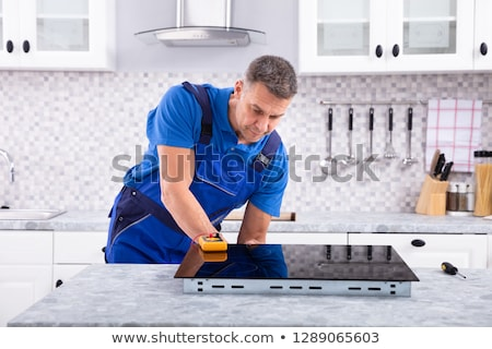 serviceman examining induction stove with digital multimeter stock photo © andreypopov