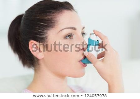 Close up of a woman using an asthma inhaler Stock photo © wavebreak_media