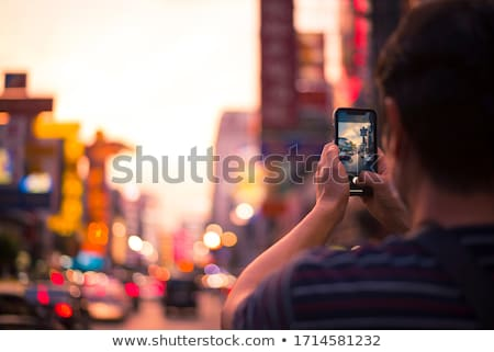 Young woman taking photo of a beautiful building Stock photo © deandrobot