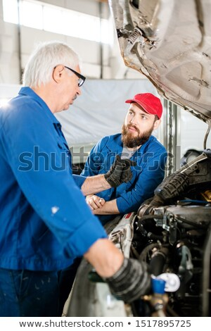 Experienced worker explaining his young colleague how to maintain vehicles Stock photo © pressmaster
