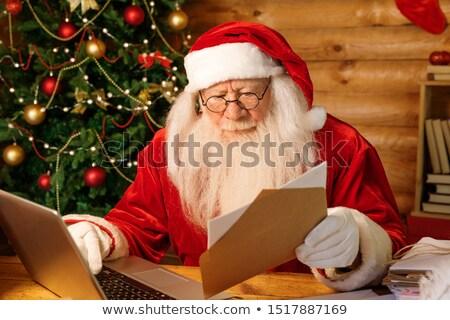 Święty mikołaj kopercie patrząc adres laptop wysłać Zdjęcia stock © pressmaster
