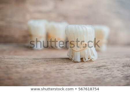 Asian uncooked noodles, tied with natural rope. Asian food concept Stock photo © galitskaya