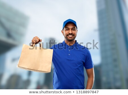 indian delivery man with food in paper bag in city Stock photo © dolgachov
