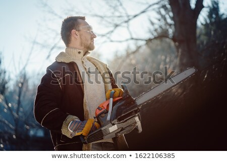 Man with a chainsaw standing in the woods ready to begin work Stock photo © Kzenon