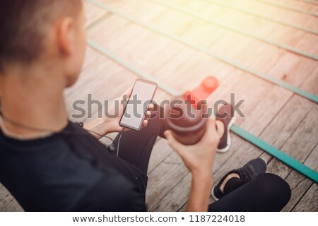 Image of young tired man using earphones and holding water bottle Stock photo © deandrobot