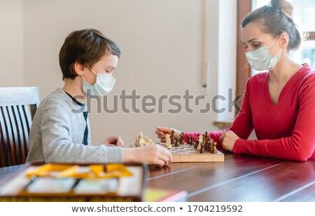 Mother and kid during coronavirus crisis playing chess at home Stock photo © Kzenon