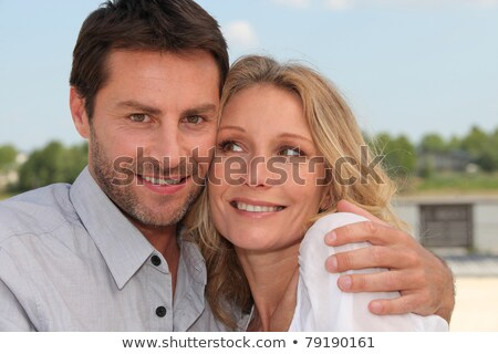 Head and shoulders of couple in tight embrace by the water Stock photo © photography33