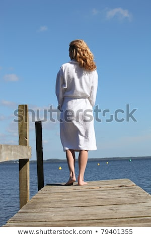 woman in a bathrobe standing on a wooden pier stock photo © photography33