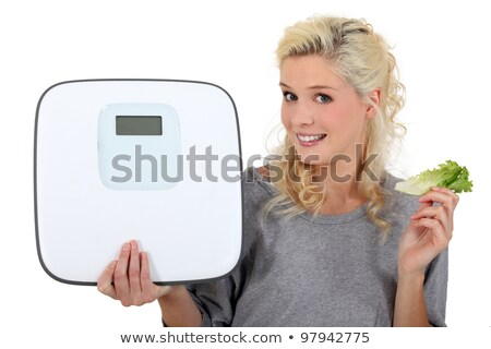 blonde woman showing a bathroom scale and taking a lettuce leave Stock photo © photography33