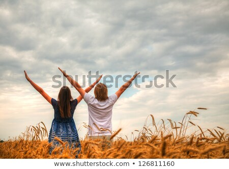 couple staying with raised hands at sunset time stock photo © andreykr