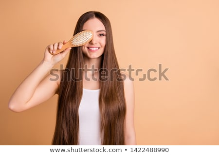 Lady's face covered with long straight hair Stock photo © stockyimages