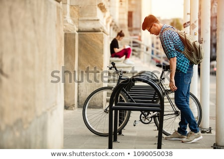 smiling man parking his bicycle stock photo © stockyimages