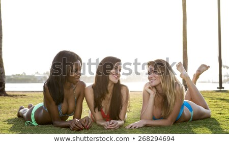 Three women lying on their belly, on the grass in a park. Backlit, looking at each other. Stock photo © BrazilPhoto