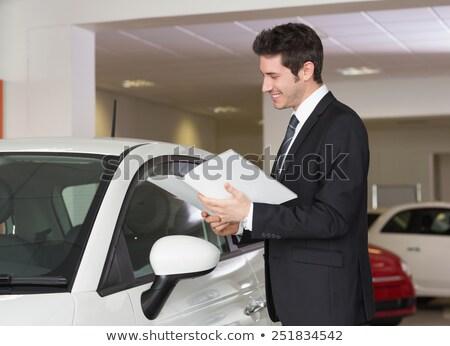 бизнесмен чтение буклет Новый автомобиль выставочный зал автомобилей Сток-фото © wavebreak_media