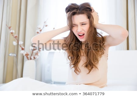 Fatigued woman sitting on bed with eard closed by hands  Stock photo © deandrobot