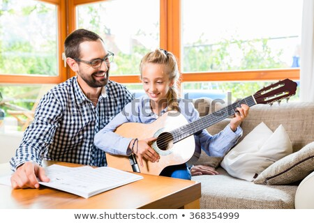 father and daughter learning play the guitar stock photo © kzenon