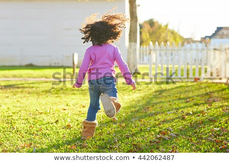 Stock photo: kid girl toddler playing running in park rear view