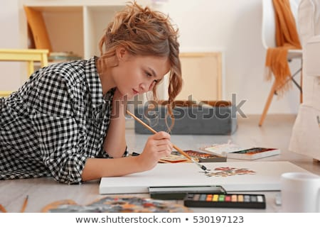 young woman paints a picture Stock photo © OleksandrO