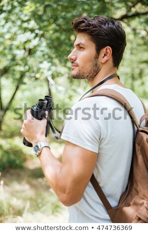 pensive young man with backpack holding binoculars in forest stock photo © deandrobot