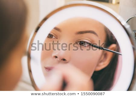 woman putting mascara in lighted makeup mirror stock photo © maridav