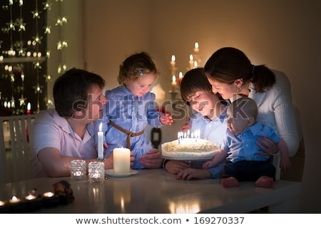 Family in living room smiling with young boy blowing out candles Stock photo © monkey_business