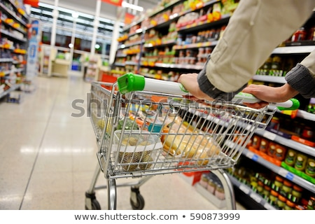 Stock photo: Woman pushing trolley along supermarket aisle