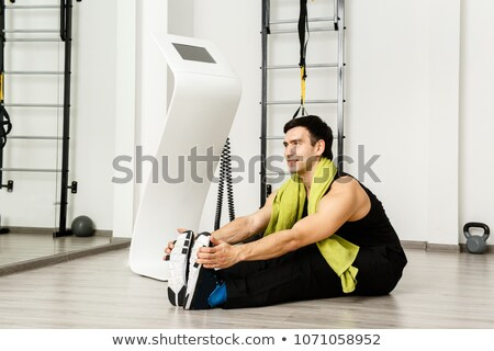 Man sitting down on exercise mat while touching his toes during stretching Stock photo © Kzenon