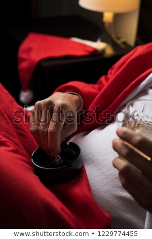 man in a santa suit drinking whisky and smoking
