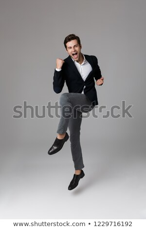 image of happy businessman 30s in formal suit yelling and clench stock photo © deandrobot