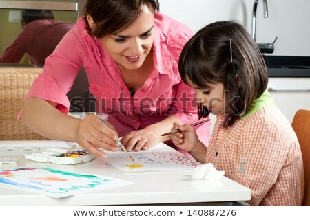 Stock photo: Mother and daughter painting together at home with paintbrushes and watercolors