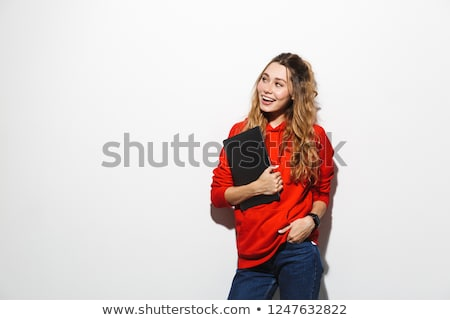Image of modern woman 20s wearing red sweatshirt holding laptop, Stock photo © deandrobot