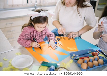 Stock photo: Mother and daughter painting together at home on the kitchen