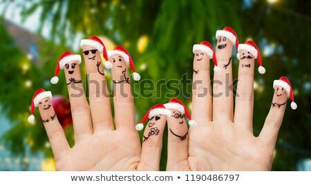 ten fingers in santa hats over christmas tree Stock photo © dolgachov