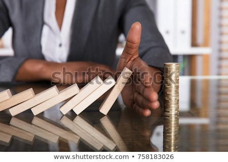 Human Hand Stopping Wooden Blocks From Falling On Stacked Coins Stock photo © AndreyPopov