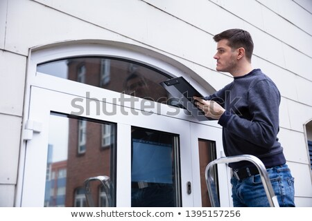 Repairman Examining The Edge Of Closed Door With Torch Stock photo © AndreyPopov