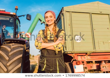 Stock photo: Farmer woman standing in front of tractor on wheat field