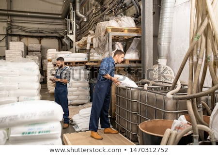 Young workers of large factory scattering polymer grains into huge container Stock photo © pressmaster