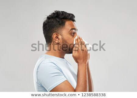 indian man with paper napkin blowing nose Stock photo © dolgachov