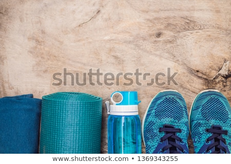 Everything for sports turquoise, blue shades on a wooden background. Yoga mat, sport shoes sportswea Stock photo © galitskaya
