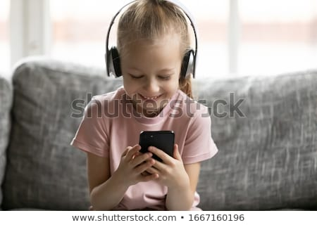 Restful girl listening to music in headphones and scrolling in smartphone Stock photo © pressmaster